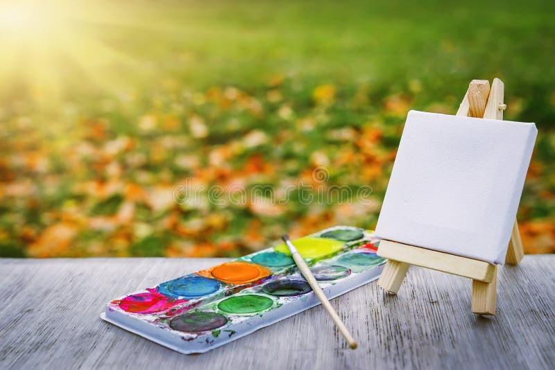 Concepto de la pintura, de la creatividad y del arte Caballete blanco con las pinturas multicoloras y cepillo en fondo de la hier fotografía de archivo libre de regalías
