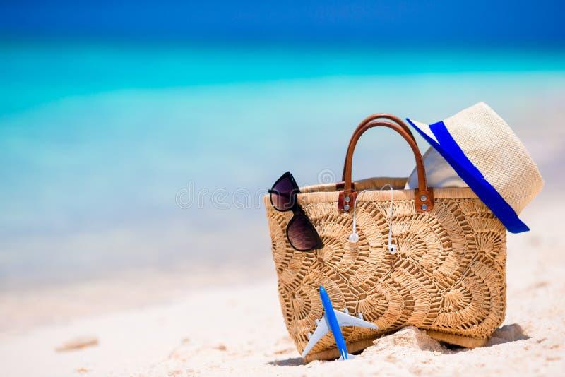 Concepto de la playa - bolso, sombrero, gafas de sol y toalla de la paja en la playa blanca foto de archivo