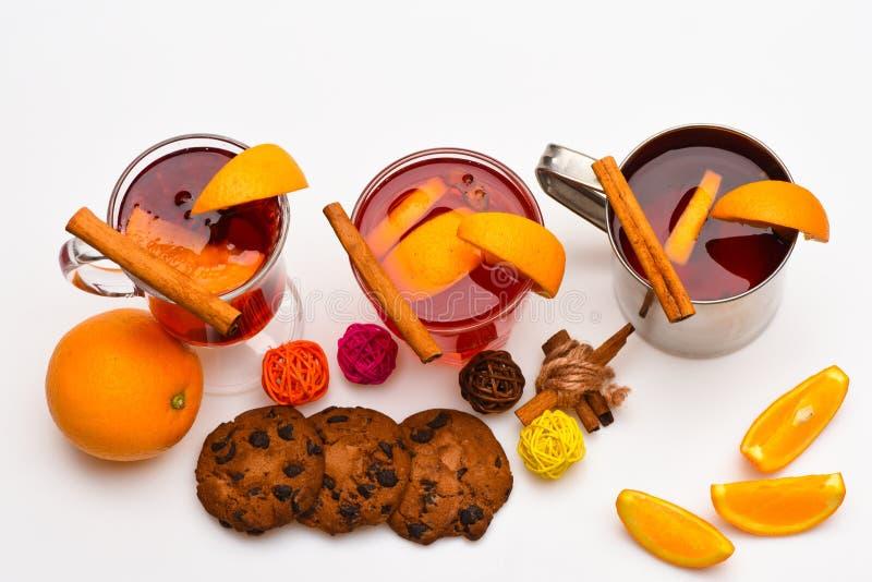 Concepto de la porción de la barra La bebida o la bebida caliente con la naranja y el canela en vidrios y metal asalta, visión su imagenes de archivo