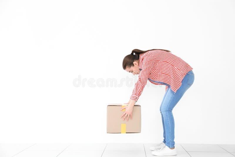Concepto de la postura Mujer joven que levanta la caja de cartón pesada imagenes de archivo