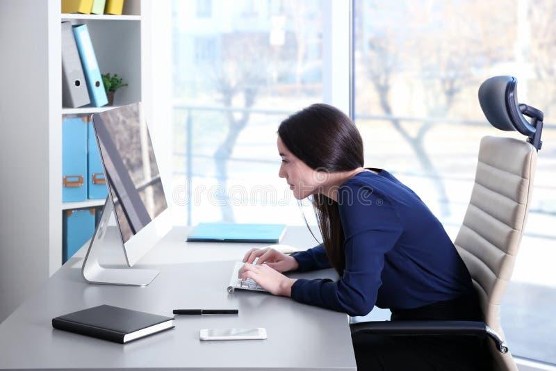 Concepto de la postura Mujer joven que trabaja con el ordenador fotos de archivo libres de regalías