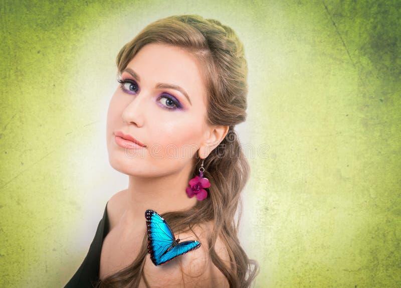 Concepto de la primavera de una mujer rubia con una mariposa azul y un flo imagen de archivo