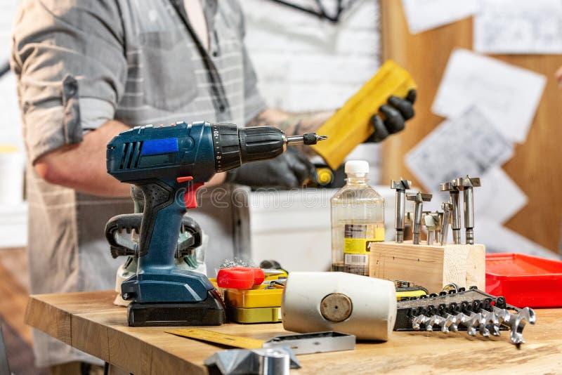 Concepto de la profesión, de la carpintería, de la artesanía en madera y de la gente - carpintero con el tablón de madera de la p imagen de archivo libre de regalías