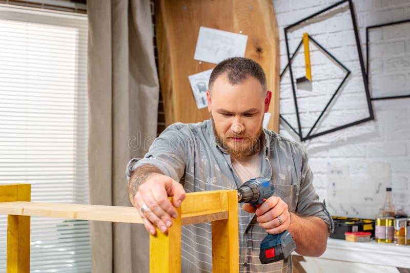 Concepto de la profesión, de la carpintería, de la artesanía en madera y de la gente - carpintero con el tablón de madera de la p fotografía de archivo