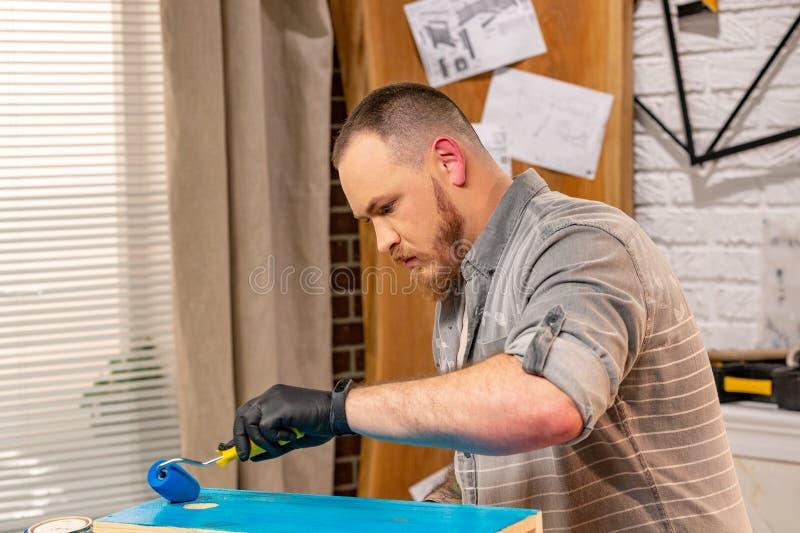 Concepto de la profesión, de la carpintería, de la artesanía en madera y de la gente - carpintero que trabaja con el tablón y las fotos de archivo libres de regalías
