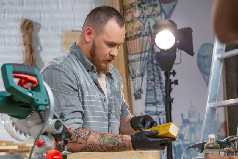 Concepto de la profesión, de la carpintería, de la artesanía en madera y de la gente - dos carpinteros con el tablón de madera de fotografía de archivo libre de regalías