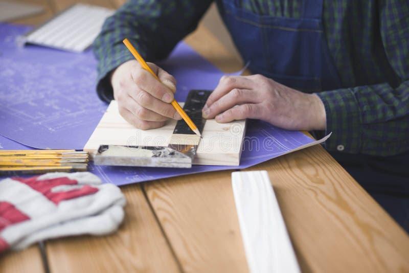 Concepto de la profesión, de la carpintería, de la artesanía en madera y de la gente - uniformidad de madera del tablón de la pru fotografía de archivo
