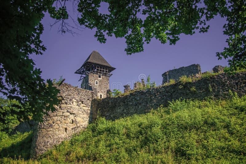 Concepto de la protección y de la defensa Torre y pared del castillo Fortalecimiento de piedra en la colina verde en el cielo azu imágenes de archivo libres de regalías