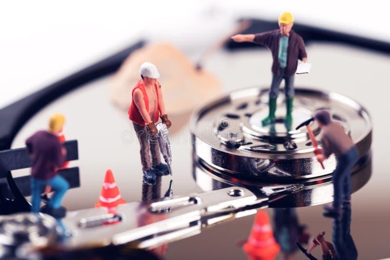 Concepto de la recuperación de los datos estatuillas del trabajador de construcción en el SID duro imagen de archivo libre de regalías