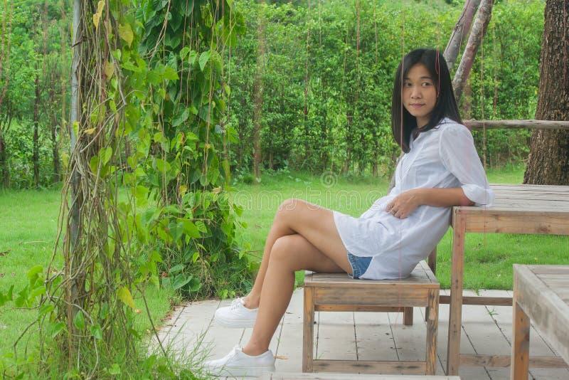 Concepto de la relajación: Mujer asiática que se sienta en silla de madera en el jardín al aire libre foto de archivo