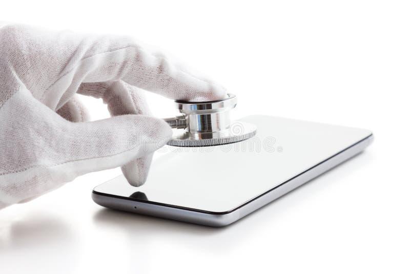 Concepto de la reparación y del servicio del teléfono Diagnósticos de Smartphone con un estetoscopio Aislado en blanco foto de archivo libre de regalías