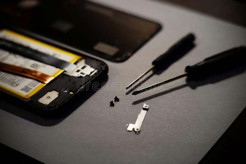 Concepto de la reparaci?n y del servicio del tel?fono Smartphone que es diagnosticado con un estetoscopio, destornilladores alred foto de archivo