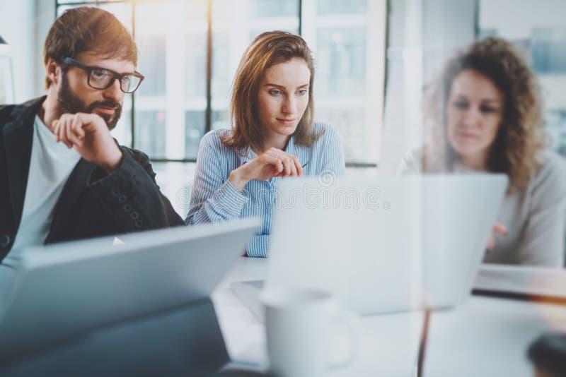 Concepto de la reunión de negocios Los compañeros de trabajo combinan el trabajo con el ordenador móvil en la oficina moderna Fon fotografía de archivo libre de regalías