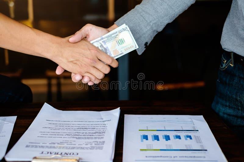 Concepto de la reunión de la sociedad del negocio Apretón de manos de los businessmans de la imagen con el dinero Corrupción y so fotografía de archivo