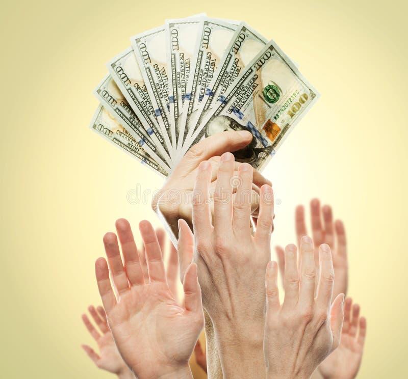Concepto de la riqueza con el dinero americano del efectivo de los dólares y muchas manos de la gente Riqueza en dólar billete de fotos de archivo libres de regalías