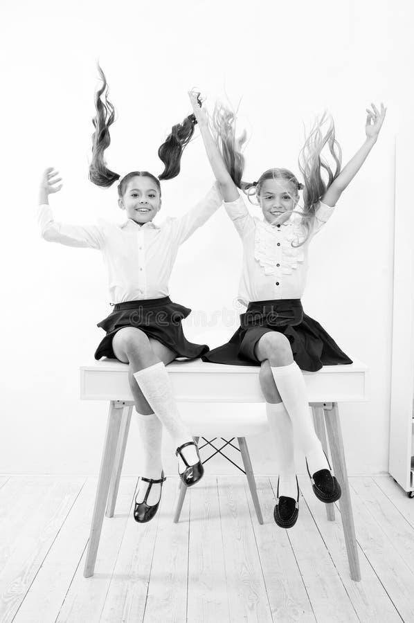 Concepto de la rotura de la escuela El peinado lindo de las colas de potro de las colegialas se sienta en el escritorio Los mejor imagen de archivo