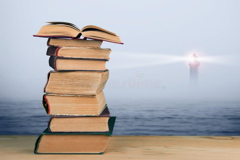 Concepto de la sabiduría - pila de libros sobre fondo del mar y del faro fotografía de archivo
