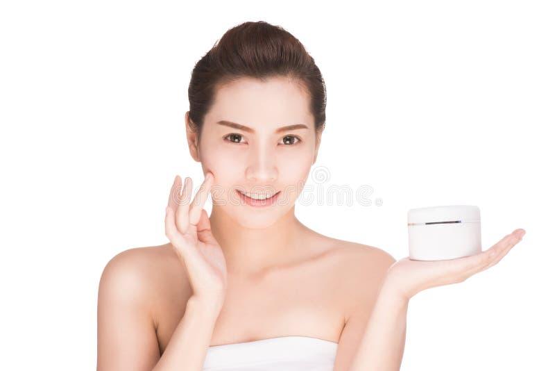 Concepto de la salud y de la belleza - mujer asiática atractiva que aplica la creatina fotos de archivo libres de regalías