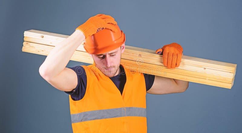 Concepto de la seguridad y de la protección El hombre en casco, casco y guantes protectores lleva a cabo el haz de madera, fondo  imagenes de archivo