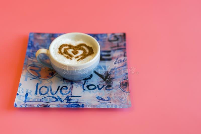 Concepto de la taza de café de la forma del corazón aislado en fondo rosado taza del amor, dibujo del corazón en el café del arte foto de archivo
