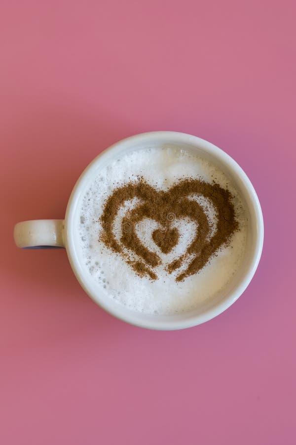 Concepto de la taza de café de la forma del corazón aislado en fondo rosado taza del amor, dibujo del corazón en el café del arte imagen de archivo libre de regalías