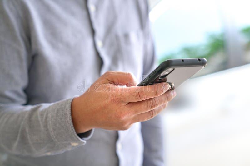 Concepto de la tecnología: Hombre de negocios que hojea o que practica surf el teléfono móvil imagenes de archivo