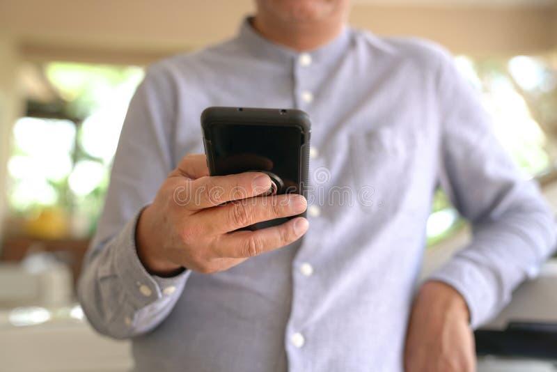 Concepto de la tecnología: Hombre de negocios que hojea o que practica surf el teléfono móvil fotografía de archivo