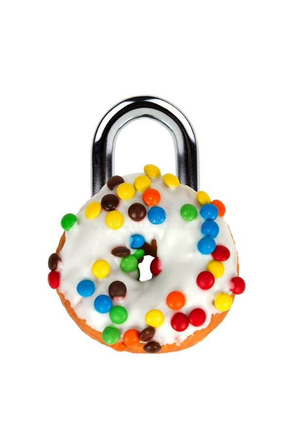 Concepto de la tentación con el buñuelo como candado foto de archivo libre de regalías