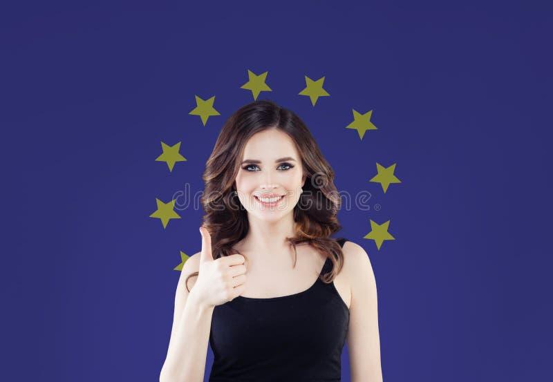Concepto de la unión europea con el pulgar feliz de la demostración de la mujer para arriba fotografía de archivo
