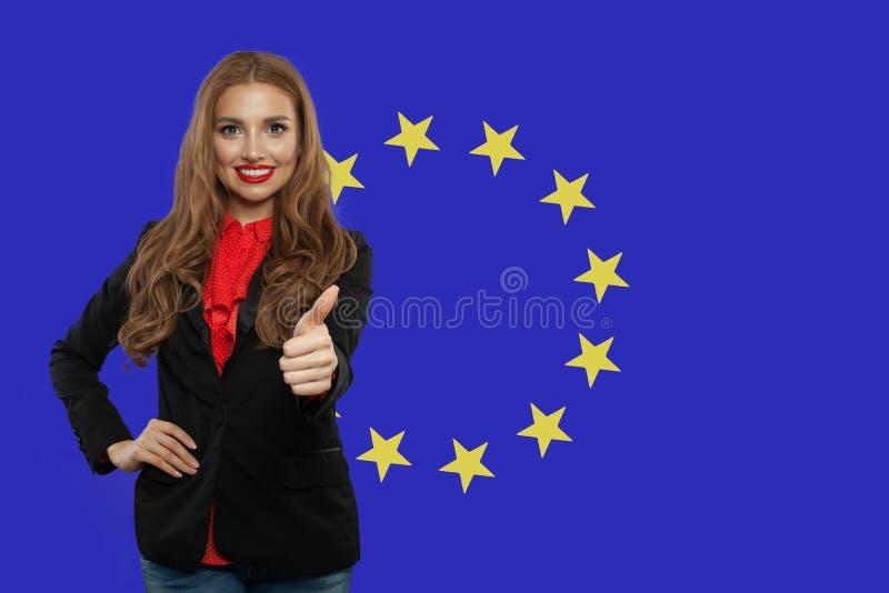 Concepto de la uni?n europea con el pulgar feliz de la demostraci?n de la mujer para arriba contra el fondo de la bandera de la U foto de archivo libre de regalías