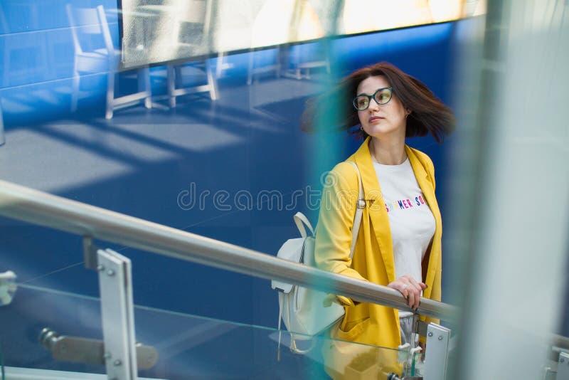 Concepto de la venta del verano Chica joven elegante en una chaqueta amarilla y vidrios en centro comercial en fondo azul con lib foto de archivo libre de regalías