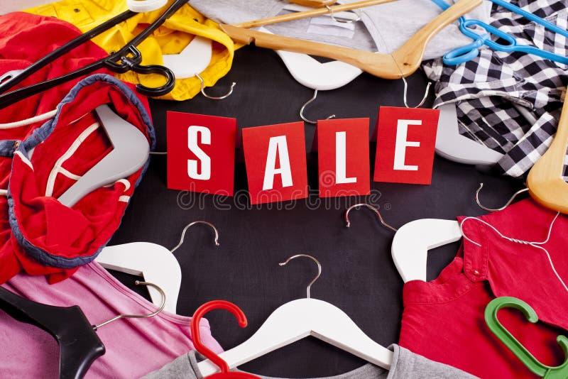 Concepto de la venta de las compras de Black Friday con la etiqueta y la ropa rojas de la venta foto de archivo