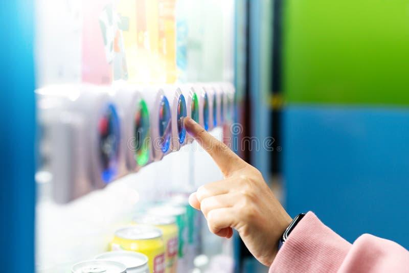 Concepto de la venta, de la tecnología y del consumo, compra de la mujer con una máquina expendedora fotografía de archivo