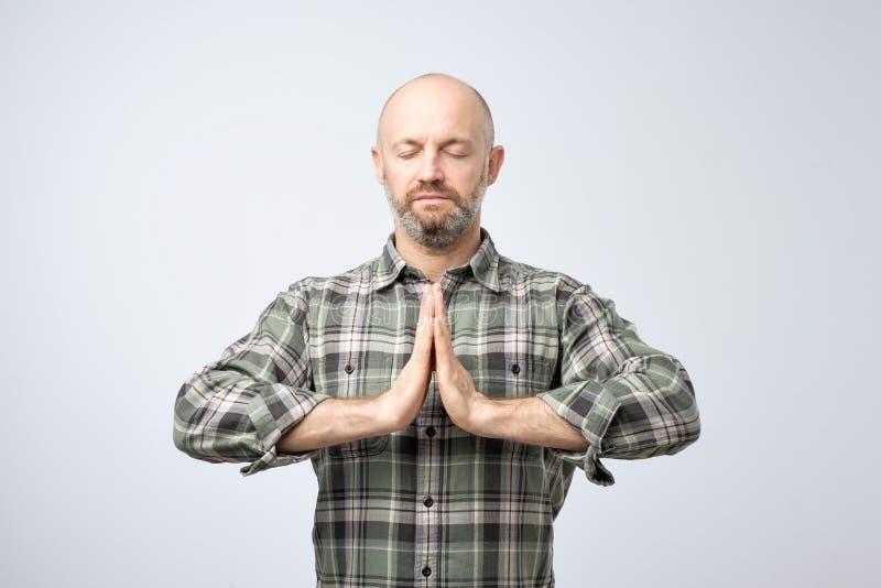 Concepto de la yoga y de la meditación Hombre calvo hermoso con la cerda que mantiene ojos cerrados mientras que medita imagen de archivo