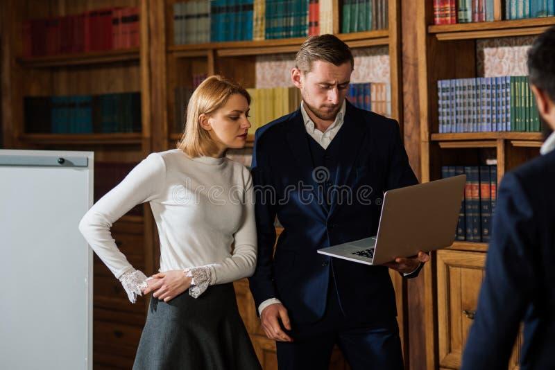 Concepto de lanzamiento Grupo de estudiantes que trabajan para el inicio acertado en biblioteca Los hombres y la mujer discuten e fotografía de archivo libre de regalías