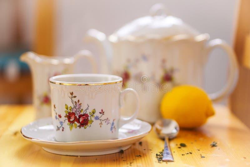 Concepto de las bebidas, de la relajación y de la fiesta del té - juego de té de taza, de pote, de cuchara, de limón y de platill imagen de archivo