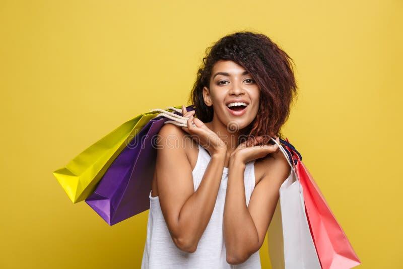 Concepto de las compras - Headshot de la mujer africana atractiva hermosa joven del retrato que sonríe y alegre con colorido imagen de archivo