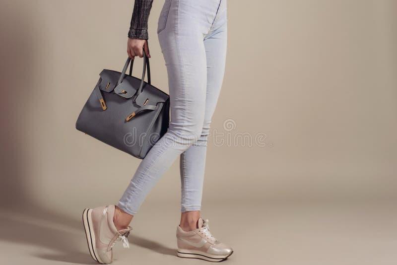 Concepto de las compras la muchacha en vaqueros y zapatillas de deporte sostiene un primer grande de moda del bolso con el espaci imagen de archivo