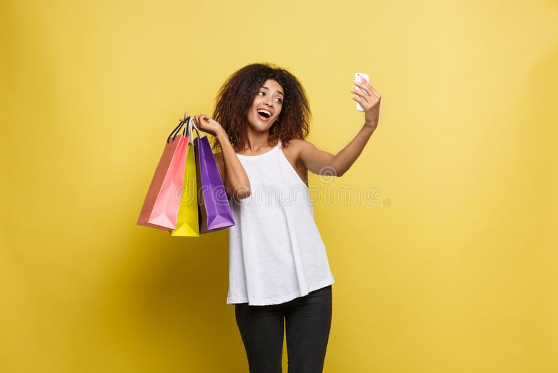 Concepto de las compras - mujer africana atractiva hermosa joven del retrato ascendente cercano que sonríe y alegre con compras c imagenes de archivo