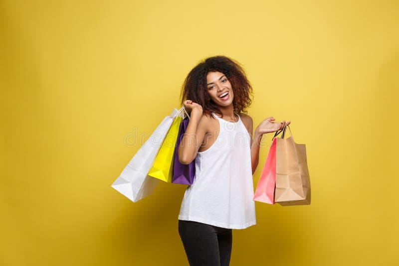 Concepto de las compras - mujer africana atractiva hermosa joven del retrato ascendente cercano que sonríe y alegre con compras c fotos de archivo libres de regalías