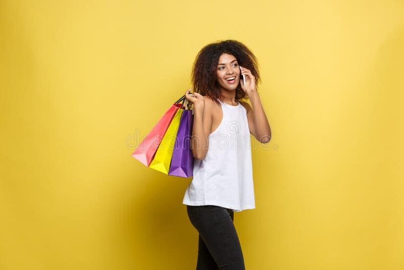 Concepto de las compras - mujer africana atractiva hermosa joven del retrato ascendente cercano que sonríe y alegre con compras c fotografía de archivo