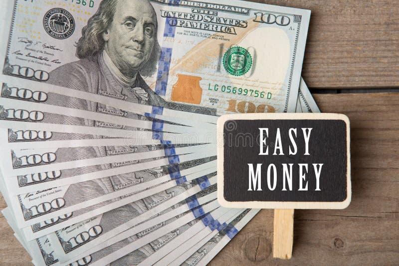 Concepto de las finanzas - pizarra con el texto y x22; money& fácil x22; y cientos billetes de dólar fotografía de archivo libre de regalías