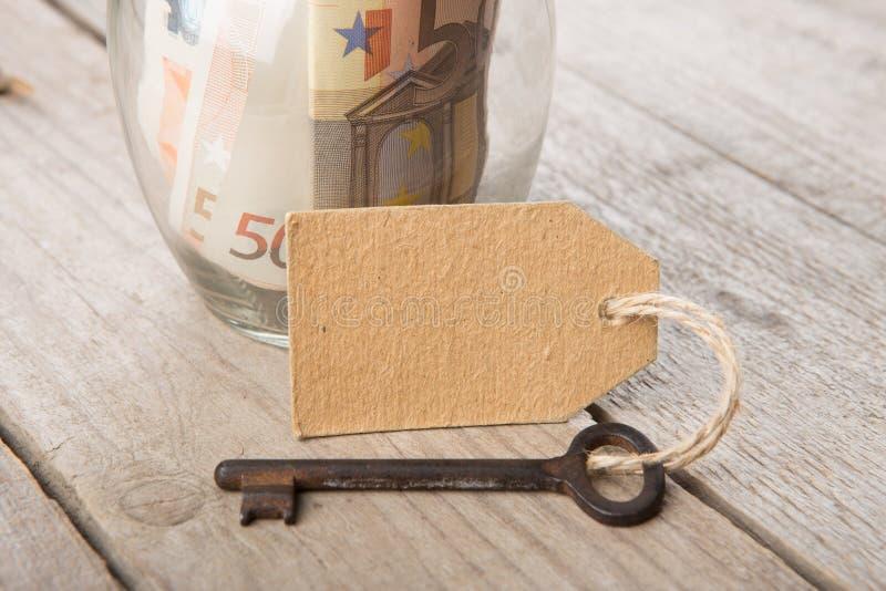 Concepto de las finanzas de las propiedades inmobiliarias - vidrio del dinero fotos de archivo libres de regalías