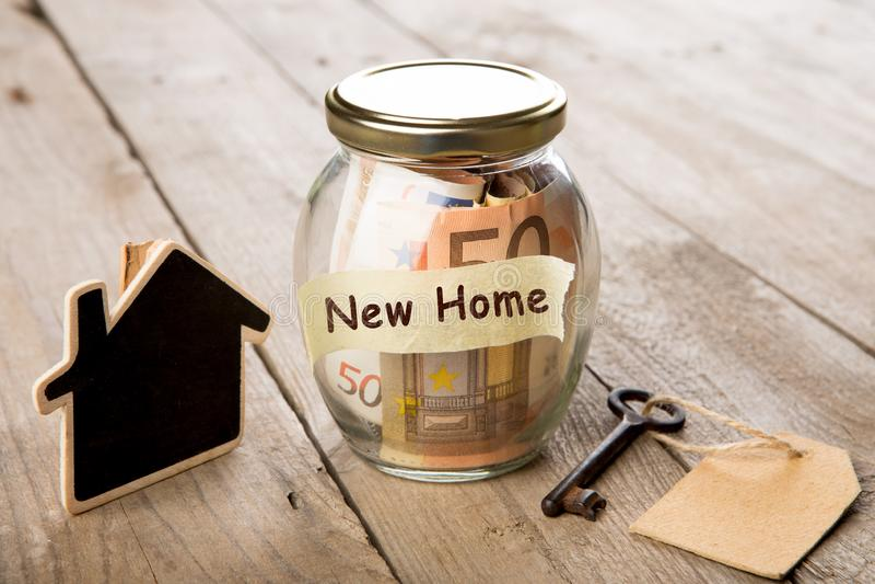 Concepto de las finanzas de las propiedades inmobiliarias - vidrio del dinero con nueva palabra casera fotografía de archivo libre de regalías
