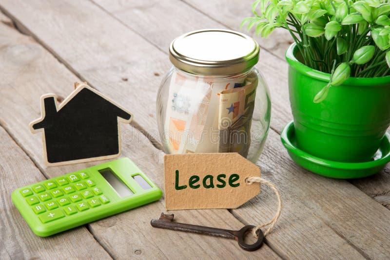 Concepto de las finanzas de las propiedades inmobiliarias - vidrio del dinero con palabra del arriendo fotografía de archivo
