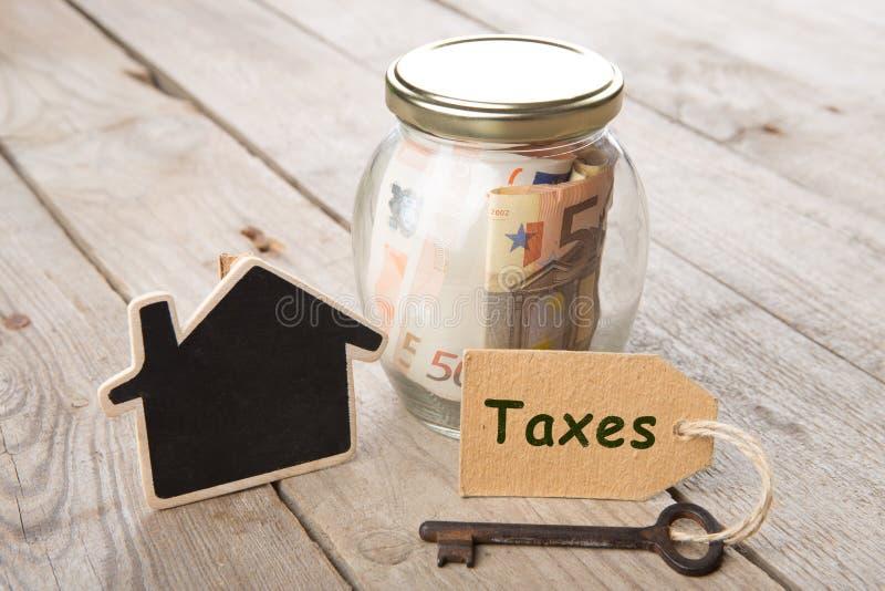 Concepto de las finanzas de las propiedades inmobiliarias - vidrio del dinero con palabra de los impuestos fotos de archivo