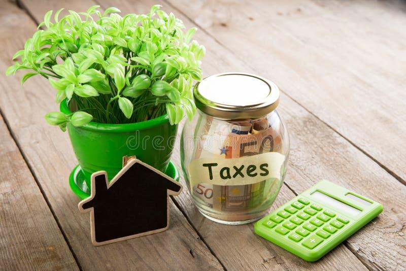 Concepto de las finanzas de las propiedades inmobiliarias - vidrio del dinero con palabra de los impuestos imagen de archivo libre de regalías