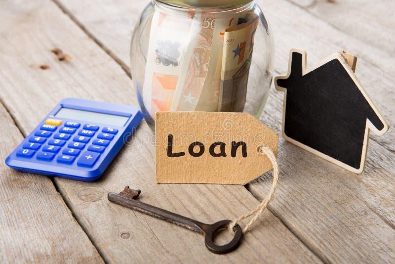 Concepto de las finanzas de las propiedades inmobiliarias - vidrio del dinero con palabra de préstamo imágenes de archivo libres de regalías