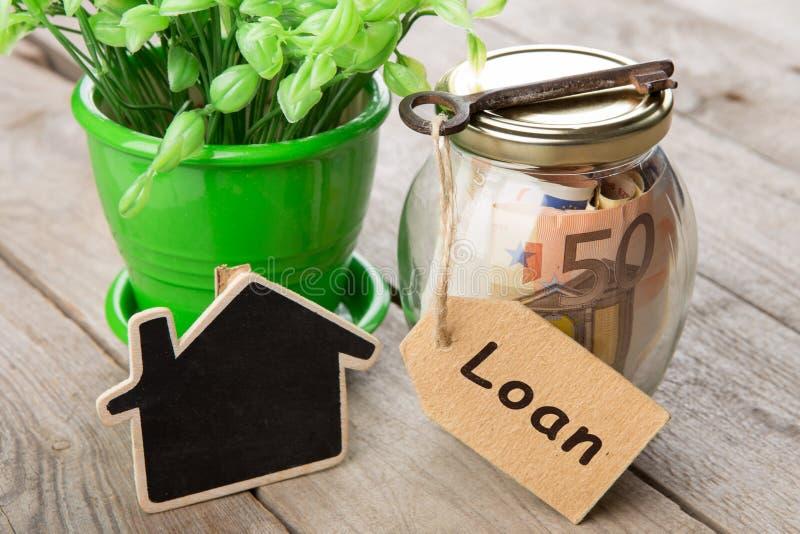 Concepto de las finanzas de las propiedades inmobiliarias - vidrio del dinero con palabra de pr?stamo foto de archivo libre de regalías