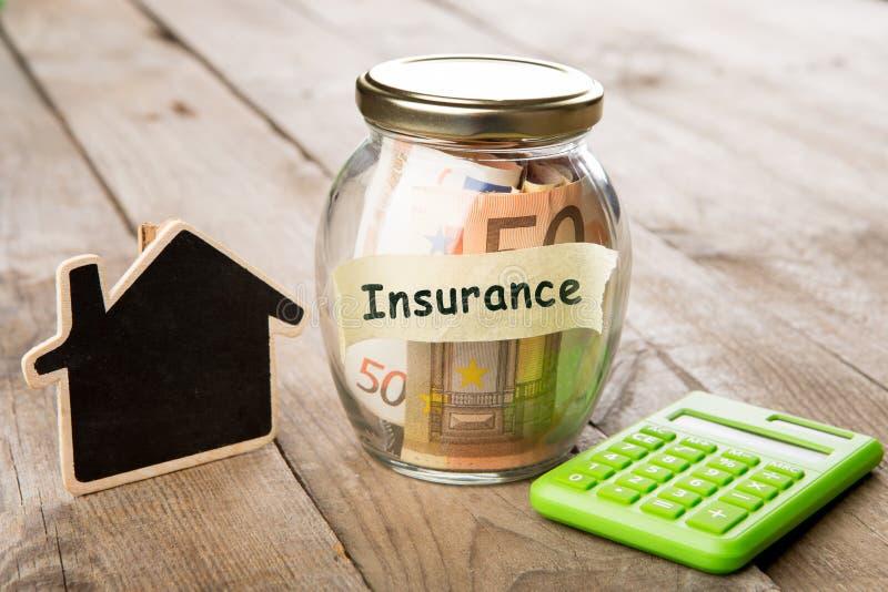 Concepto de las finanzas de las propiedades inmobiliarias - vidrio del dinero con palabra del seguro fotos de archivo